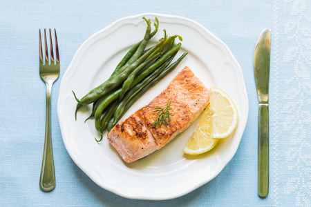 Grilled salmon fillet with green beans and lemon on white plate from above