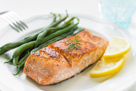 cooked fish: Close up of grilled salmon fillet with green beans and lemon on white plate Stock Photo