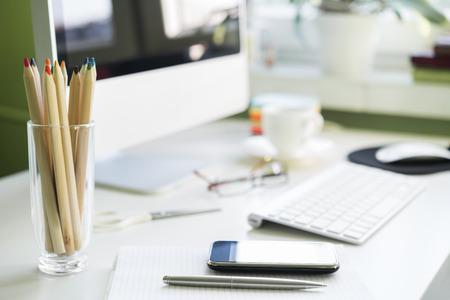 白いテーブルでコンピューターと仕事場。スマート フォンに焦点を当てる