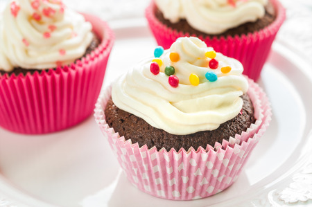 party tray: Fancy chocolate cupcakes with vanilla cream and colorful toppings and decoration