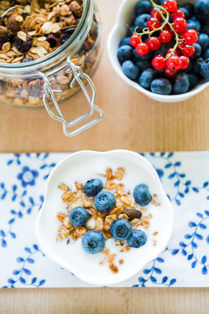 closeup view: Healthy breakfast with granola, blueberries and redcurrant. Top view close-up