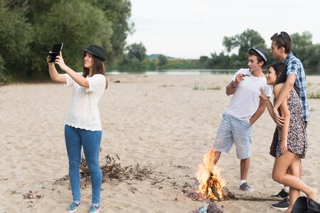 bonfires: A group of teenage friends having fun and taking selfies outdoor