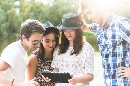 lifestyle caucasian: Young adult friends taking selfies with tablet and having fun outdoors