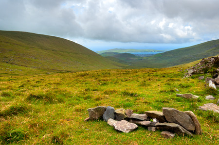 a meadow: Green valleys with hills and lakes with moody sky over Ring of Kerry in County Kerry, Ireland
