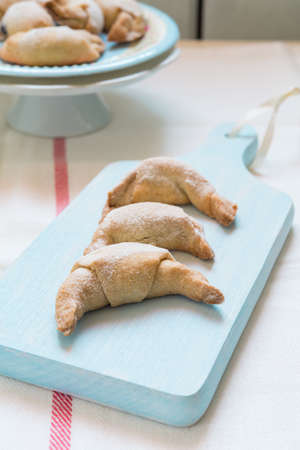 short crust pastry: Freshly baked short crust pastry crescent rolls topped with ice sugar on a colorful plate and a wooden cutting board