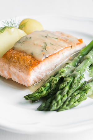 garnished: Close up of grilled salmon fillet with potatoes and asparagus garnished with dill sauce arranged on white plate