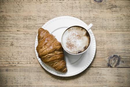 De kop van latte macchiatokoffie met croissant op witte plaat schikte op oude rustieke houten lijst. Bovenaanzicht Stockfoto