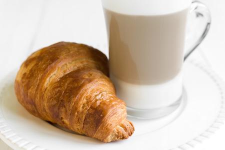 Croissant en glas latte koffie op een witte plaat en tafel