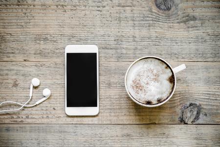 Kop van lattekoffie met witte moderne smartphone en oortelefoons op oude rustieke houten lijst. Bovenaanzicht Stockfoto