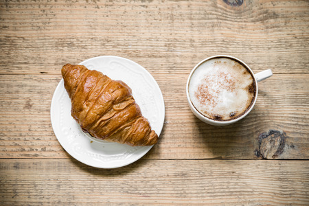 Cup of latte coffee with croissant on white plate arranged on old rustic wooden table. Top view 版權商用圖片