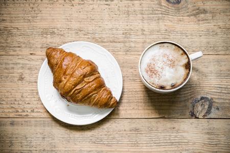 Kop van latte koffie met croissant op witte plaat aangebracht op oude rustieke houten tafel. bovenaanzicht