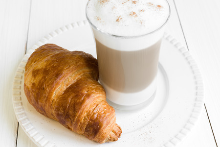 Croissant and glass of latte macchiato coffee arranged on white plate and white table