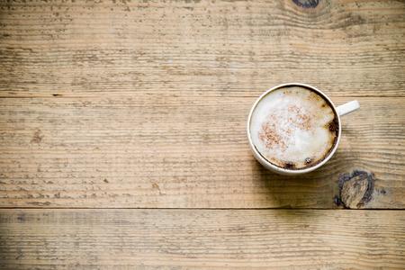 Kopje cappuccino of latte koffie op houten tafel. Bovenaanzicht met een kopie ruimte