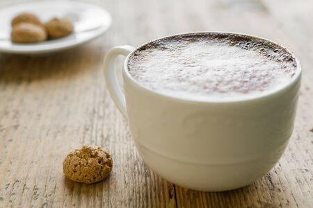 Kop van latte koffie met biscotti gerangschikt op oude rustieke houten tafel Stockfoto