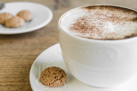 Kop van latte macchiato koffie met biscotti gerangschikt op oude rustieke houten tafel Stockfoto