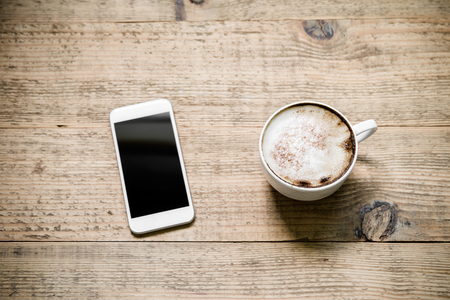 Cup of latte coffee with white modern smartphone on old rustic wooden table. Top view