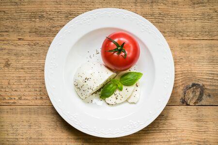 Mozzarella met tomaat, verse basilicum, olijfolie en kruiden als ingrediënten voor caprese salade. Bovenaanzicht.