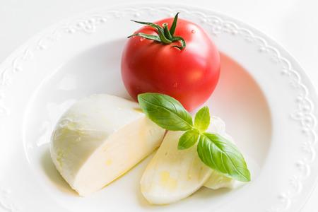 Sluit omhoog van mozarellakaas met tomaat, verse basilicum en olijfolie als ingrediënten voor caprese salade op witte plaat. Stockfoto