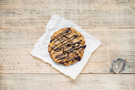 oatmeal cookie: Oatmeal cookie with chocolate topping arranged on baking paper and old rustic table. top view. Stock Photo