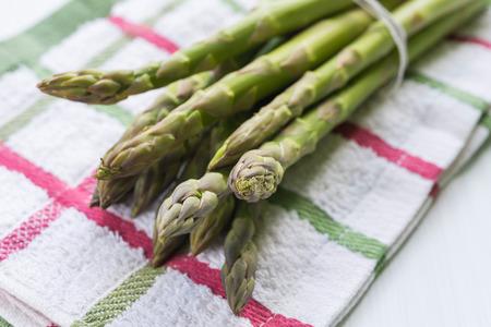 Close up of fresh asparagus bunch arranged on stripped kitchen cloth 版權商用圖片
