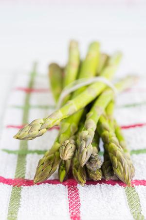 Close-up van verse asperge bos gerangschikt op gestripte keukendoek Stockfoto