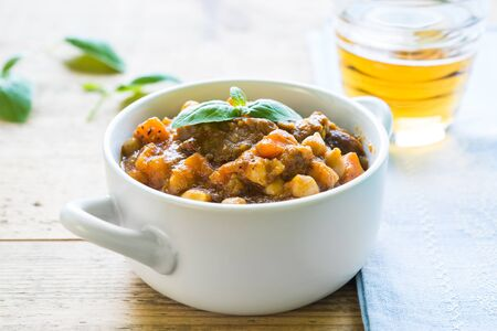 Close up of beef stew with chickpeas and carrots topped with fresh basil served in a white bowl on a wooden table