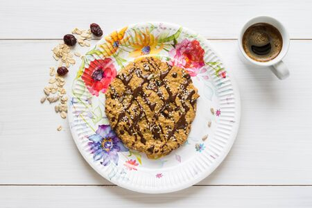 Top view of an oatmeal cookie on a colorful plate with a cup of black coffee and oatmeal and cranberry scattered around it on a white wooden table