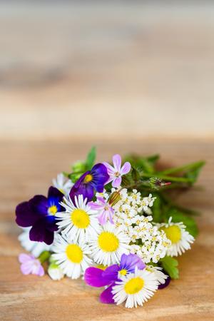 Boeket van kleurrijke tuinbloemen op houten lijst met exemplaarruimte. Selectieve aandacht.