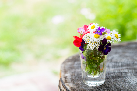 Closeup of colourful garden flowers in a glass on old wooden tree trunk with copy-space. Selective focus 版權商用圖片