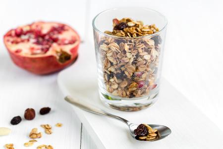 Verse muesli van granola in een glas met amandelen, rozijnen en granaatappel. Gezond ontbijt.