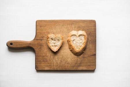 Hoogste mening van twee stukken van vers gesneden brood in een hart-vormige natuurlijke vorm op scherpe raad met witte achtergrond. Hou van concept.