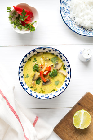 Thai coconut milk soup with chicken meat, mushroom, coriander, red pepper and rice noodles in colorful bowl on white table. Top view.