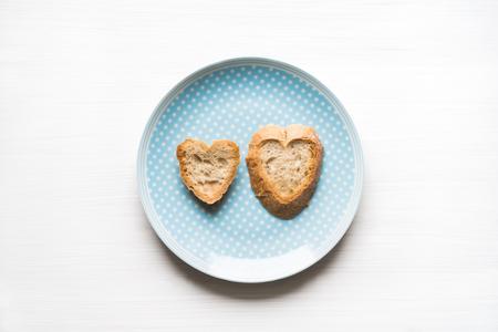 Hoogste mening van natuurlijk hart-vormig gesneden brood op blauwe plaat met witte achtergrond. Hou van concept.