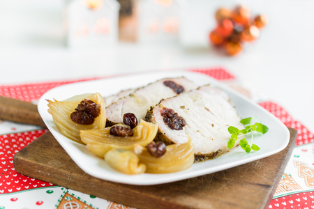 Slices of roasted pork chops stuffed with cranberries and garlic with cooked onion and fresh oregano on white plate arranged on rustic cutting board.