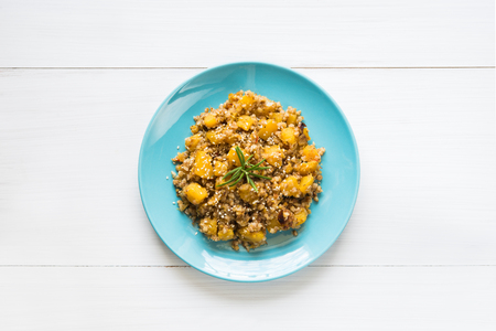Top view of fresh buckwheat stew with pumpkin, sesame and rosemary on blue plate and white table background