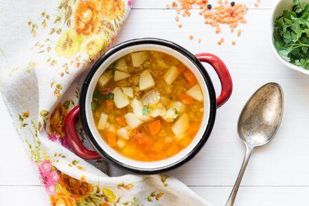 Hoogste mening van vegetarische erwtensoep met rode linze en verse peterselie op witte houten lijst Stockfoto