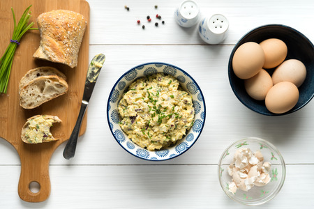 Homemade egg salad spread with mayonnaise, mustard, red onion sprinkled with chives, top view background on white table.