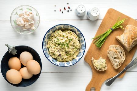 Eigengemaakte eisalade die met mayonaise, mosterd, rode die ui wordt verspreid met bieslook wordt bestrooid, hoogste meningsachtergrond op witte lijst. Stockfoto