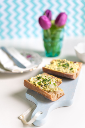 Close-up of fresh baguette sandwich spread with with egg salad on blue cutting board with bunch of tulips in background
