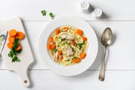 Fresh chicken soup with vegetables and pasta in a bowl with carrot and parsley on white table, top view
