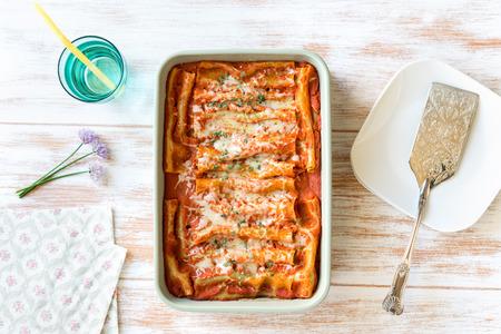 Bovenaanzicht van zelfgemaakte cannelloni gevuld met spinazie en ricotta