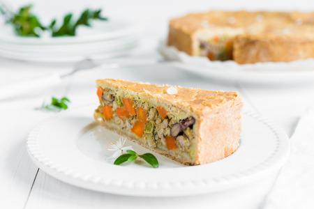 Close-up van een stuk van vleespastei die met groenten, wortelen, rode bonen en erwten wordt gebakken die op witte plaat en houten lijst worden geschikt