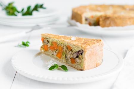 dept: Closeup of a piece of meat pie baked with vegetables, carrots, red beans and peas arranged on white plate and wooden table