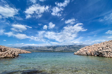 Quiet bay with Paklenica National Park Mountains in background. Beautiful ocean and dramatic blue sky with clouds on hot summer day. Stockfoto