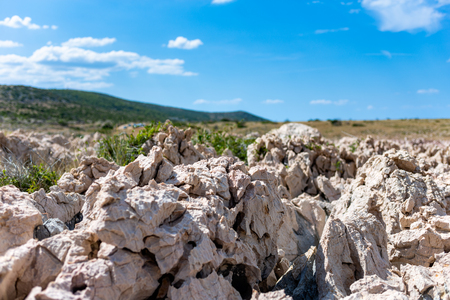 Selective focus on rocks structure on Dalmatian coastline on Hvar. Sunny day with blue sky - shallow dept of field. Stockfoto