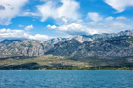 Paklenica National Park Mountains with beautiful ocean and dramatic blue sky with clouds on hot summer day. Stockfoto