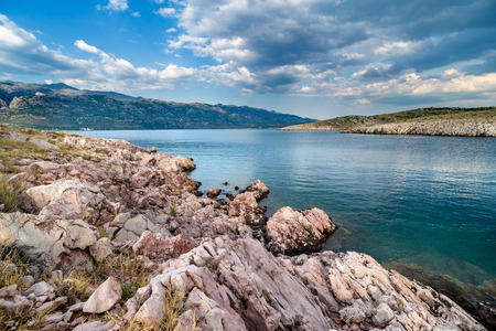 Beautiful ocean and dramatic blue sky with clouds on hot summer day., rain in background over Paklenica National Park Mountains.
