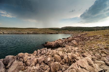 Moody ocean and dramatic dark clouds with rain over picturesque hills in Dalmatia, Croatia.