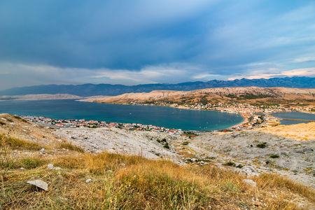 Wide angle scenic view over village on Pag island in the evening with sea and cloudy sky.