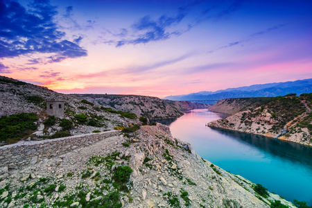 Colorful evening scenic view from Maslenica bridge over the river and mountains with dramatic sunset sky in Dalmatia, Croatia. Wide angle, long exposure and color grad filters used.
